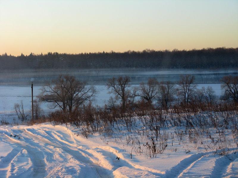Зимний вид на затуманенную предсумеречную долину реки